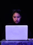 Portrait of a beautiful and smart girl hacker with laptop on dark background with using glasses in her head Stock Images