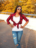 Portrait beautiful smiling african woman wearing a sunglasses, red checkered shirt posing in sunny autumn Stock Photography
