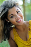 Portrait of a beautiful smiling biracial woman. Beautiful young biracial woman - outdoor portrait wearing a yellow blouse smiling stock photo