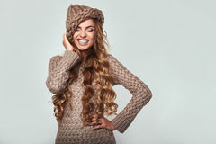 Portrait of beautiful smiling blond woman. With long hair, brown sweater and hat Stock Images