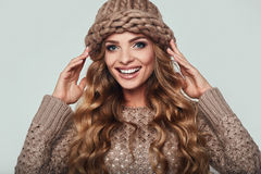 Portrait of beautiful smiling blond woman. With long hair, brown sweater and hat Stock Photo