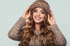 Portrait of beautiful smiling blond woman. With long hair, brown sweater and hat Royalty Free Stock Photography