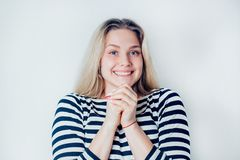 Portrait of beautiful smiling blonde woman in striped dress on white background with copy space. Young girl happy and very happy. royalty free stock photo