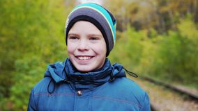 Portrait of beautiful smiling boy with blue eyes in autumn park, close-up stock images