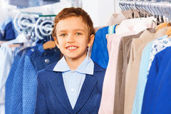 Portrait of beautiful smiling boy near clothes Stock Photography