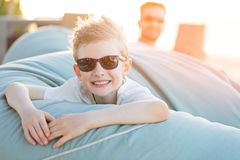 Family of two at vacation. Portrait of beautiful smiling boy in sunglasses enjoying tropical vacation with his father in the background Royalty Free Stock Photo