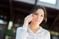 Beautiful smiling businesswoman on the phone in a office buildin Royalty Free Stock Photography