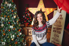 Portrait of beautiful smiling curly women near christmas tree. Celebration. Funny. Throw pillow Stock Photos