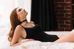Portrait of beautiful smiling exotic young woman lying in bed in her underwear with choker Stock Photography