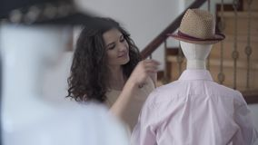 Portrait cute young smiling female fashion designer or stylist fitting shirt on mannequin with fedora hat in showroom or. Portrait of beautiful smiling female stock footage