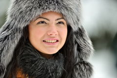 Portrait of beautiful smiling female wearing luxurious fur cap Stock Photo