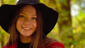 Portrait of a beautiful smiling girl in a black hat with a yellow maple leaf in the foreground in the autumn forest. Weekend outside the city stock footage