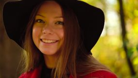 Portrait of a beautiful smiling girl in a black hat with a yellow maple leaf in the foreground in the autumn forest. Weekend outside the city. Slow motion stock video footage