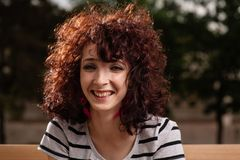 Portrait of beautiful smiling girl with curly red hair close up Stock Image