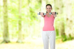 Portrait of beautiful smiling girl with dumbbells Stock Images