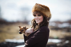 Portrait of a beautiful smiling girl in a fur hat with little do Stock Photos