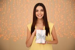 Portrait of beautiful smiling girl with gift box on blurred background. stock photography