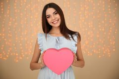 Portrait of beautiful smiling girl with heart shaped gift box on blurred background. royalty free stock photography