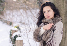 Portrait of a beautiful smiling girl near the tree in winter Stock Image