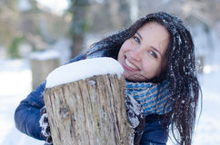 Portrait of a beautiful smiling girl near the wooden column in winter Stock Photography