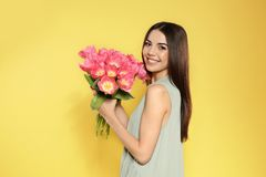 Portrait of beautiful smiling girl with spring tulips on yellow background. stock image