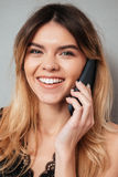 Portrait of a beautiful smiling girl talking on mobile phone. Close up portrait of a beautiful smiling girl talking on mobile phone isolated over grey background Stock Photo