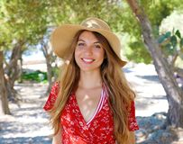 Portrait of a beautiful smiling girl wearing hat and red dress looking at camera outdoors stock image