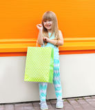 Portrait of beautiful smiling little girl child. With shopping bag against the colorful orange wall Royalty Free Stock Images