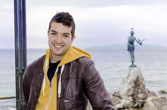 Portrait of beautiful smiling man posing for photo. Portrait of beautiful young tourist man in front of the maiden with the seagull statue in Opatia , Croatia royalty free stock image