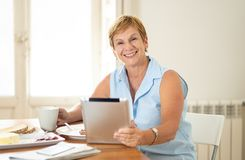 Portrait of a happy senior woman using electronic tablet at home. Portrait of a beautiful smiling mature woman using digital tablet while having breakfast and Royalty Free Stock Photos