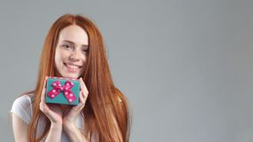 Portrait of beautiful smiling redhead girl hold gift box in hands. stock footage