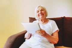 Portrait of beautiful smiling senior woman with the ipad. royalty free stock image