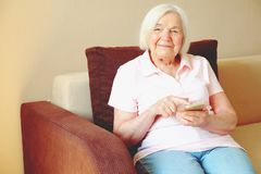 Portrait of beautiful smiling senior woman with the smartphone royalty free stock photo