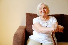 Portrait of a beautiful smiling senior woman with walking cane on light background at home royalty free stock image