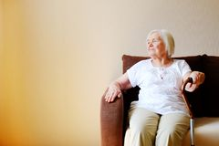 Portrait of a beautiful smiling senior woman with walking cane on light background at home stock photography