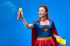 Portrait of beautiful smiling superwoman with rag and detergent for cleaning. Isolated on blue stock photos