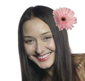 Portrait of beautiful smiling woman #2. Portrait of a beautiful smiling woman with brown eyes and a pink Gerbera flower with long brown hair on white background Royalty Free Stock Image