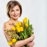 Portrait of a beautiful smiling woman with a bouquet of flowers Stock Images