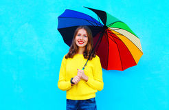 Portrait beautiful smiling woman with colorful umbrella in autumn day over colorful blue background Stock Image