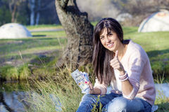 Portrait of beautiful smiling woman counting money in the park Stock Photo