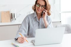 Portrait of beautiful smiling woman in glasses taking notes while speaking on mobile phone, indoors stock photography