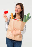 Portrait of beautiful smiling woman holding shopping paper bag with organic fresh food isolated on white background. Royalty Free Stock Photo