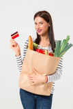 Portrait of beautiful smiling woman holding shopping paper bag with organic fresh food isolated on white background. Stock Photography