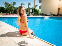 Portrait of beautiful smiling young woman with long hair sitting on the poolside and holding feet in water. Girl stock image