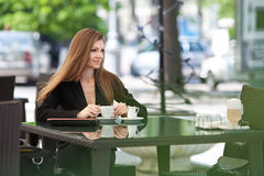 Portrait of beautiful smiling woman sitting in a cafe with laptop outdoor Royalty Free Stock Photo