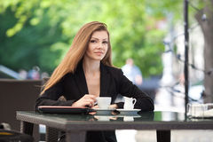 Portrait of beautiful smiling woman sitting in a cafe with laptop outdoor Stock Images