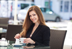 Portrait of beautiful smiling woman sitting in a cafe with laptop outdoor Royalty Free Stock Image