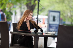 Portrait of beautiful smiling woman sitting in a cafe with laptop outdoor Stock Photos