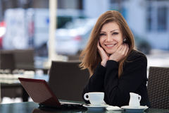 Portrait of beautiful smiling woman sitting in a cafe with laptop outdoor Stock Photo