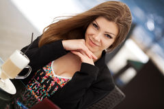 Portrait of beautiful smiling woman sitting in a cafe with laptop outdoor. Portrait of a beautiful brunette with long hair sitting in an outdoor cafe for a Royalty Free Stock Photography